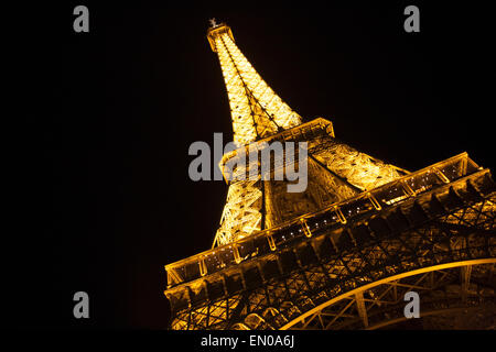 An angled view of the Eiffel Tower all lit up at night in Paris France. - Stock Photo