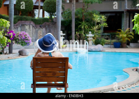 woman relaxing in luxury spa hotel near beautiful swimming pool - Stock Photo