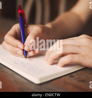 kid writes in notepad - Stock Photo