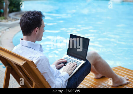 business man with laptop in luxury hotel near swimming pool - Stock Photo