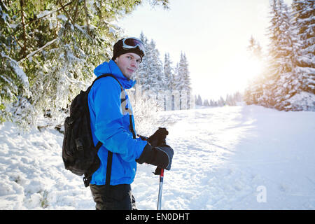 portrait of young handsome skier in winter forest - Stock Photo