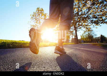 close up feet of runner at sunset - Stock Photo