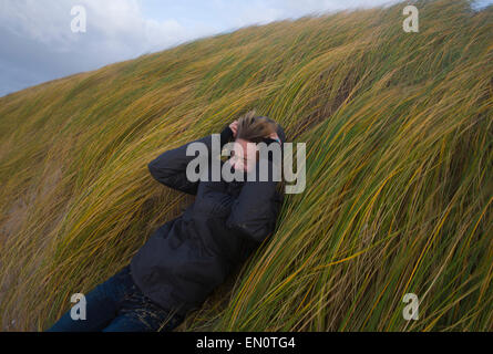 Dutch woman holding up against in wind - Stock Photo