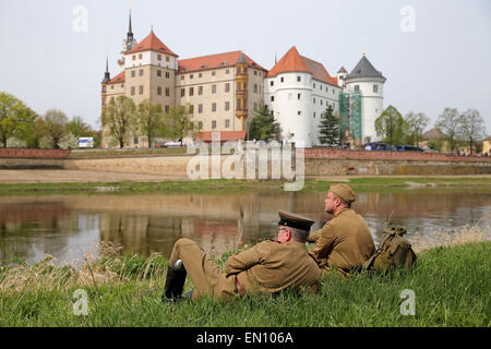 Torgau, Germany. 25th Apr, 2015. Participants of a reenactment of the World War II liberation sit next to the river - Stock Photo