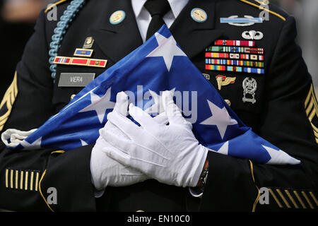 Torgau, Germany. 25th Apr, 2015. A US soldier holds a folded flag of the United States during a ceremony entitled - Stock Photo