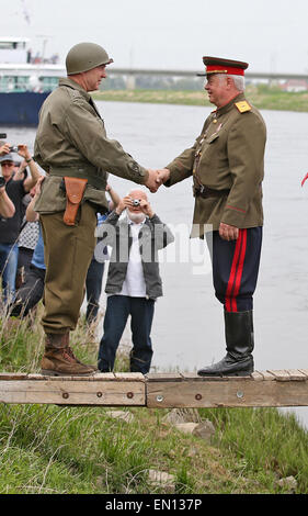 Torgau, Germany. 25th Apr, 2015. Two men reenact a historic meeting between Soviet and US soldiers toward the end - Stock Photo