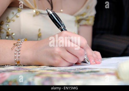Bride signing the marriage certificate after the wedding - Stock Photo