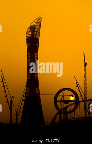 The sun sets behind the Aspire hotel tower in Doha, Qatar, with cranes involved in work on the Khalifa football - Stock Photo