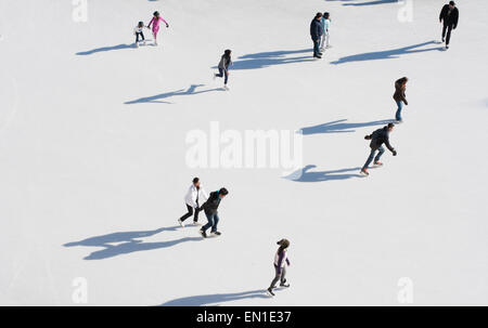 Aerial view of people skating in community rink during winter holiday season - Stock Photo