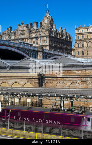The Flying Scotsman standing at Edinburgh's Waverley Station with the Balmoral hotel in the background. - Stock Photo