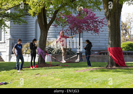Group of friends slacklining at Cal Anderson Park - Seattle, King County, Washington, USA - Stock Photo