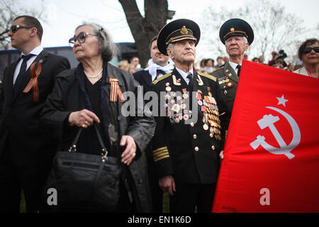 Torgau, Germany. 25th Apr, 2015. A former Soviet veteran wearing his medals holds a flag during celebrations of - Stock Photo