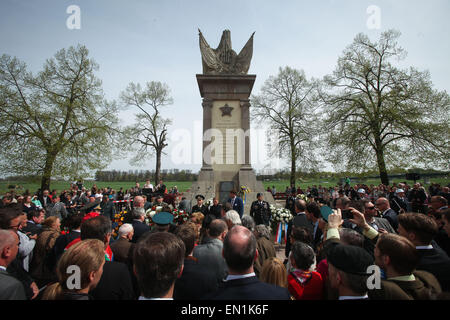 Torgau, Germany. 25th Apr, 2015. Visitors put a flower wreath in front a monument during celebrations of the 70th - Stock Photo