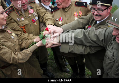 Torgau, Germany. 25th Apr, 2015. Amateur actors wearing military uniforms of allied forces hold a rose together - Stock Photo