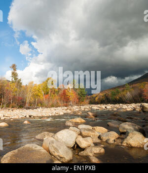 Sun highlights the autumn trees while dark clouds gather over the scenic cool, Pemigewasset River, Route 112, Bear - Stock Photo