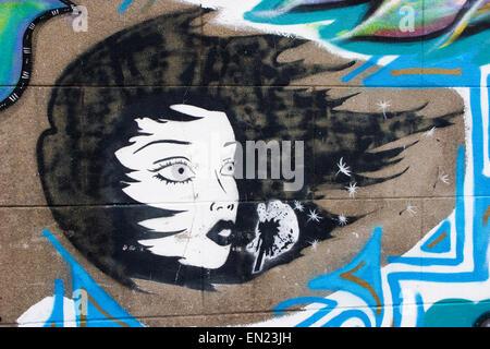Street art in Brookfield Avenue (off Gloucester Road), Bristol: blowing on a dandelion clock - making a wish - Stock Photo