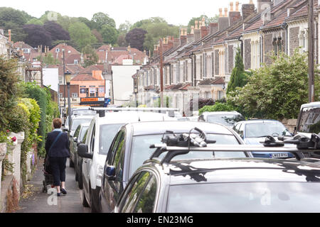 Woman with pram negotiating cars parked partially on the pavement, in Wolseley Road, Bishopston, Bristol - Stock Photo