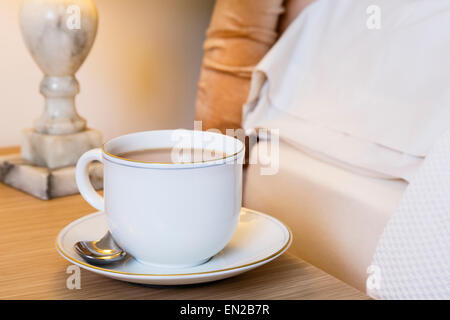 Morning cup of English tea on a bedside table at side of a bed. Everyday lifestyle. England UK Britain - Stock Photo