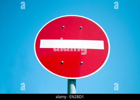 Red and white no entry road sign against blue sky - Stock Photo