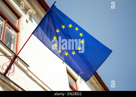 Blue with yellow stars european union flag hanging from building - Stock Photo