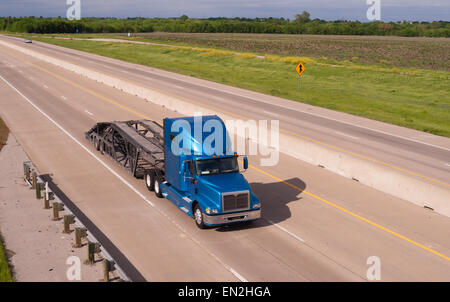 A big Rig car hauler rolls down the highway headed to pick up the next cargo - Stock Photo