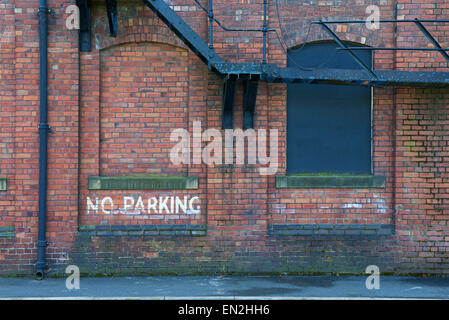 No parking sign on industrial brickwork building, - Stock Photo