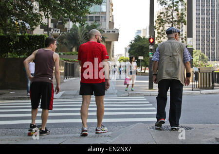 SAO PAULO, BRAZIL - FEBRUARY 08, 2015: An unidentified group of people waiting to cross a street in the corner Paulista - Stock Photo