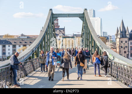 People on the old iron bridge (Eiserner Steg) over the river Main in Frankfurt Main, Germany - Stock Photo