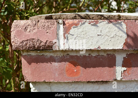 paint peeling off due to weathering - red brick garden wall gatepost cap requiring maintenance and repainting - Stock Photo
