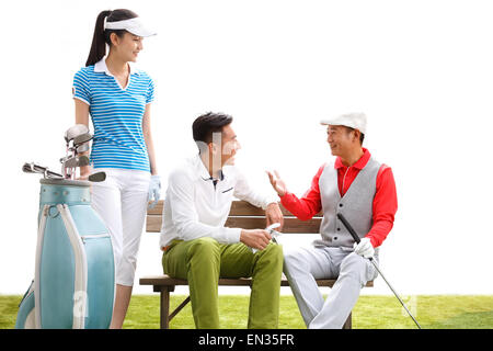 Golfers are sitting talking on the bench - Stock Photo