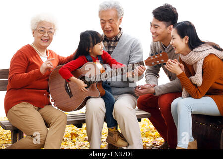Happy family outdoor play the guitar - Stock Photo