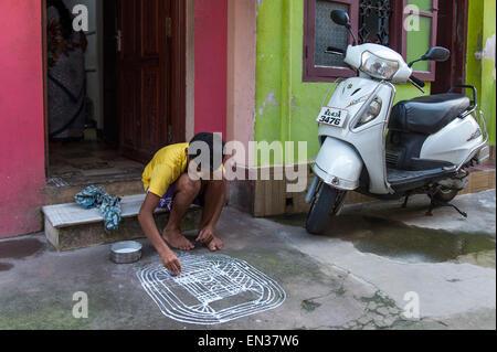 Boy painting a traditional Rangoli, Kolam or Muggu, decorative pattern of coloured sand, Tamil quarter, Mattancherry, - Stock Photo