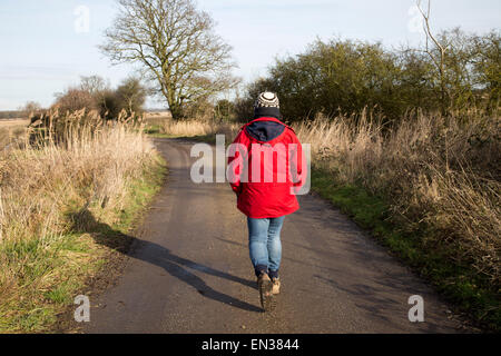 Model released woman walking along country track, Butley, Suffolk, England, UK - Stock Photo