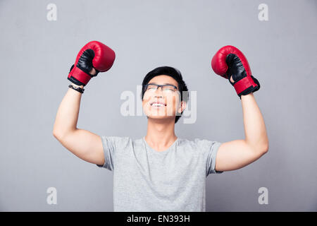 Asian man in boxing gloves rejoices victory over gray background - Stock Photo