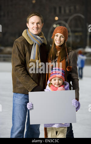 Man and woman with girl holding blank sign outdoors in winter - Stock Photo