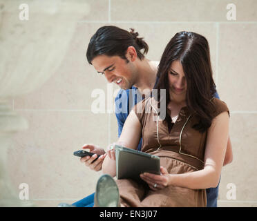 France, Paris, Young couple sitting in Louvre Museum - Stock Photo