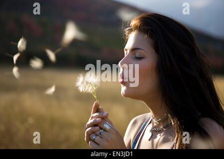 USA, Utah, South Fork, Teenage girl (16-17) blowing dandelion in meadow - Stock Photo
