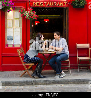 France, Paris, Young couple sitting in sidewalk cafe - Stock Photo