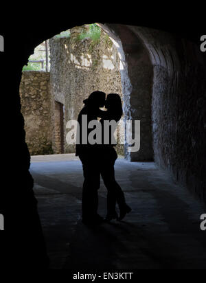 Italy, Ravello, Silhouettes of couple kissing in gate - Stock Photo