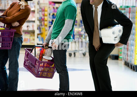 People waiting in line with shopping baskets at grocery store - Stock Photo