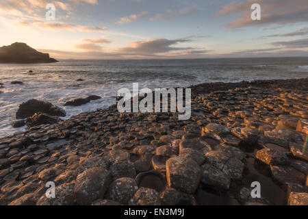 Member of the public takes a photograph of the sunset over Giant's causeway in County Antrim on the northeast coast - Stock Photo