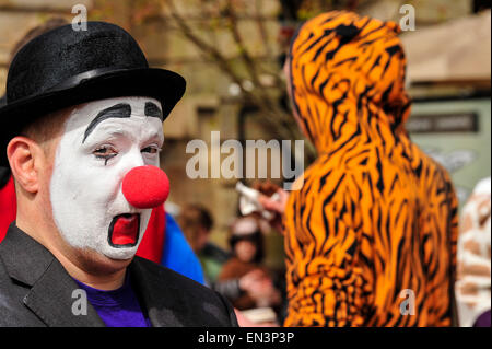 Clown with white painted face and red nose wearing a hat in the Guildhall Square, Derry, Londonderry, Northern Ireland. - Stock Photo