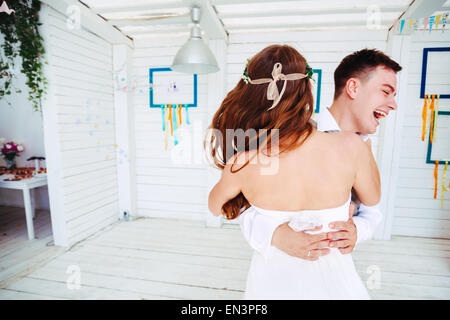 Happy young wedding couple, laughing and dancing. Selective focus on bride. - Stock Photo