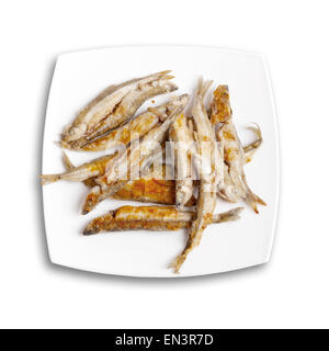 Pile of fried smelts fish lays on a white plate, top view isolated on white background with soft shadow - Stock Photo