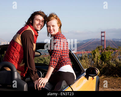 USA,California,San Francisco,Young couple in convertible car,with Golden Gate Bridge in background - Stock Photo