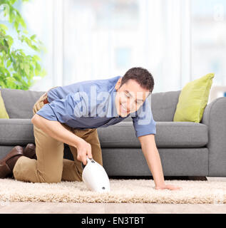 Young man vacuuming a carpet with a handheld vacuum cleaner and smiling at home - Stock Photo