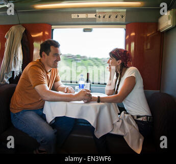 Italy, Venice, Mature couple holding hands while sitting inside of dinning car - Stock Photo