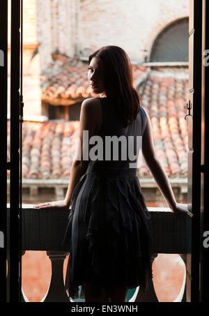 Italy, Venice, Young woman standing in balcony door - Stock Photo