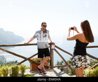 Italy, Amalfi Coast, Ravello, Woman taking picture of men - Stock Photo