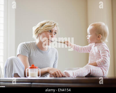 mother and baby girl at the breakfast table - Stock Photo